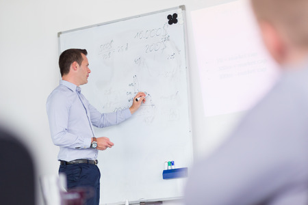 Businessman writing on whiteboard during his presentation on in-house business training, explaining business plans to his employees.