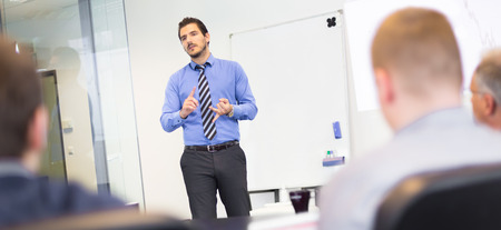 Business man making a presentation at office. Business executive delivering a presentation to his colleagues during meeting or in-house business training, explaining business plans to his employees. Foto de archivo