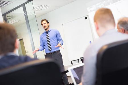 Bedrijfs mens die een presentatie op kantoor. Business executive leveren van een presentatie aan zijn collega's tijdens de vergadering of in-house business training, leggen business plannen om zijn werknemers.
