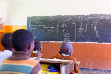 Ländliche afrikanische Schule mit Schulkindern an ihren Schreibtischen im Klassenzimmer in Nord-Tansania, Afrika. Standard-Bild