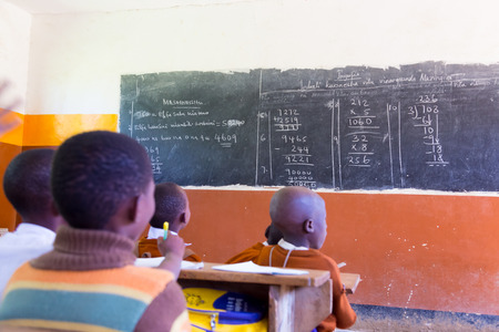 african village: Rural african school with school children at their desks in classroom in North Tanzania, Africa. Stock Photo