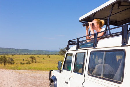 holiday trip: Young blond lady on safari standing in open roof car observing wild animals through binoculars.