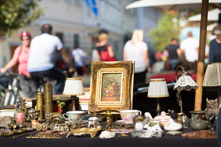 antique booth: Market boot with objects beeing selled at the weekend flea market in the city center. Curious visitors in the background.