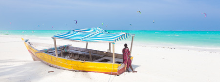 maasai: Maasai warrior lounging aroundon traditional colorful wooden boat on picture perfect tropical sandy beach on Zanzibar, Tanzania, East Africa. Kiteboarding spot on Paje beach.