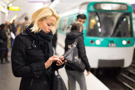 到着する電車の駅のプラットフォームで待っている彼女の手に携帯電話で冬のコートの若い女性。公共交通機関。