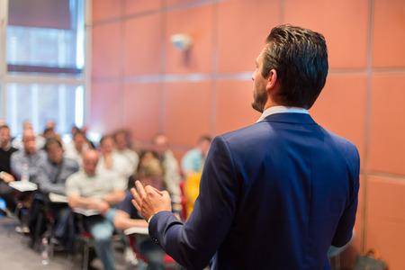 hablar en publico: Ponente en la Conferencia de negocios con presentaciones públicas. Audiencia en la sala de conferencias. Club de Emprendimiento. Vista trasera. Composición Horisontal. Desenfoque de fondo.