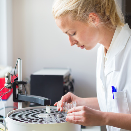 Focused attractive young life science professional working in analytical laboratory. Focus on the researchers face.