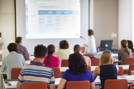 participants: Speaker giving presentation in lecture hall at university. Participants listening to lecture and making notes. Stock Photo