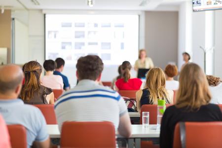 Spreker geeft presentatie in collegezaal op de universiteit. De deelnemers luisteren naar een lezing en het maken van notities.