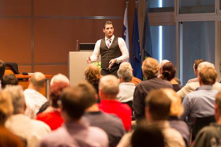 ビジネス会議やプレゼンテーションでスピーカー。会場に観客。ビジネスと起業家精神。