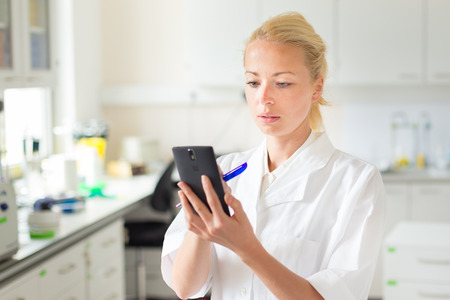 health care professional: Portrait of an attractive, young, confident female health care professional in his working environment making notes on her smarth phone. Stock Photo