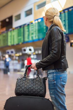 cronogramas: Vestido con ropa informal joven viajero con estilo femenino comprobación de un tablero de salidas en la sala de la terminal del aeropuerto en frente de la verificación en couters. Pantalla Horario de vuelo borroneada en el fondo. Centrarse en la mujer.