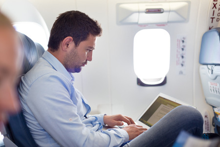 Casually dressed middle aged man working on laptop in aircraft cabin during his business travel. Shallow depth of field photo with focus on businessman eye. photo