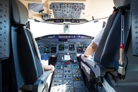 Rear view of pilot and copilot flying comercial airplane. Interior of airplane cockpit. Instrument panels in pilots cabin.
