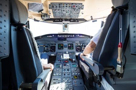 piloto de avion: Vista trasera del piloto y el copiloto del vuelo del avión comercial. Interior de la cabina del avión. Paneles de instrumentos en los pilotos de la cabina.