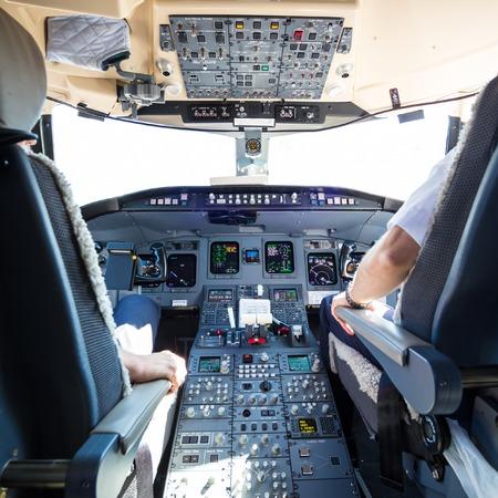 piloto: Vista trasera del piloto y el copiloto del vuelo del avión comercial. Interior de la cabina del avión. Paneles de instrumentos en los pilotos de la cabina.