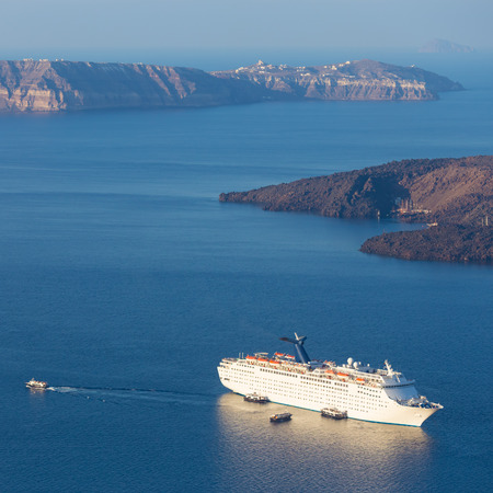 caribbean cruise: Luxury cruise ship sailing around Santorini island, Aegean sea in Greece. Stock Photo