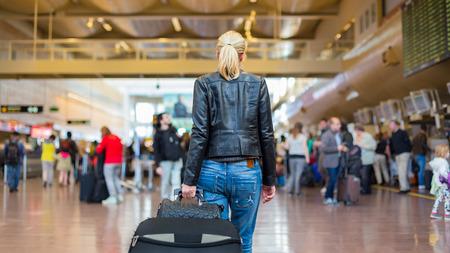 passenger buses: Vestido con ropa informal joven viajero con estilo femenino caminar la maleta sala terminal del aeropuerto arrastrando y un bolso detrás de ella. Fondo desenfocada. También puede ser utilizado como tren, metro, estación de autobuses.