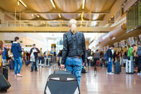 verjas: Vestido con ropa informal joven viajero con estilo femenino caminar la maleta sala terminal del aeropuerto arrastrando y un bolso detrás de ella. Fondo desenfocada. También puede ser utilizado como tren, metro, estación de autobuses.