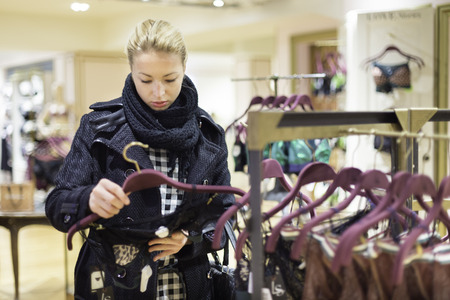 woman clothes: Woman shopping lingerie . Shopper looking and choosing clothing indoors in store. Beautiful blonde caucasian female model wearing winter coat and fashionable knitted cap.