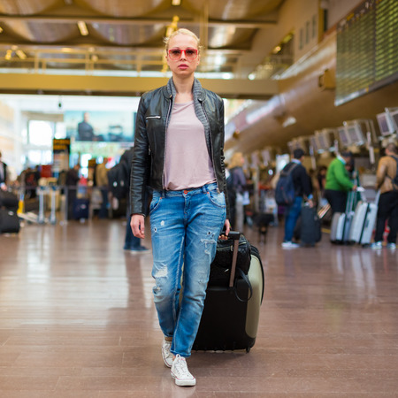 casually: Casually dressed young stylish female traveller walking the airport terminal hall   draging suitcase and a handbag behind her. Blured background. Can also be used as railway, metro, bus station. Stock Photo