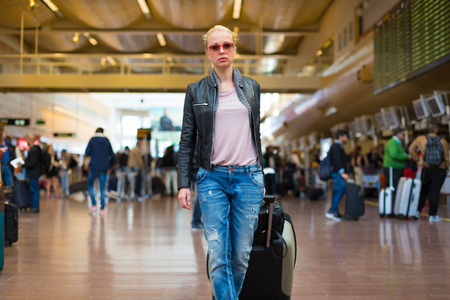 check in: Casually dressed young stylish female traveller walking the airport terminal hall   draging suitcase and a handbag behind her. Blured background. Can also be used as railway, metro, bus station. Stock Photo