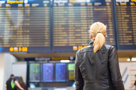 cronograma: Vestido con ropa informal joven viajero con estilo femenino comprobación de un tablero de salidas en la sala de la terminal del aeropuerto en frente de la verificación en couters. Pantalla Horario de vuelo borroneada en el fondo. Centrarse en la mujer.