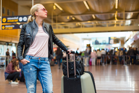 departures board: Casually dressed young stylish female traveller checking a departures board at the airport terminal hall in front of check in couters. Flight schedule display blured in the background. Focus on woman.