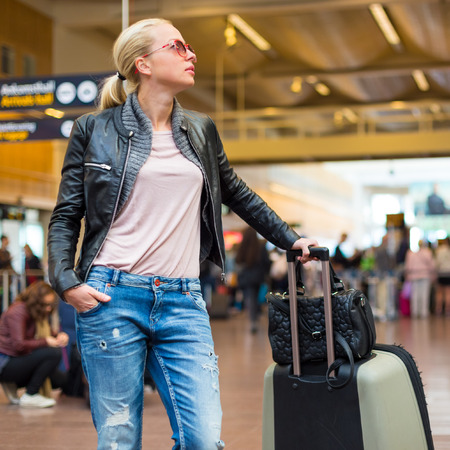 check in: Casually dressed young stylish female traveller checking a departures board at the airport terminal hall in front of check in couters. Flight schedule display blured in the background. Focus on woman.