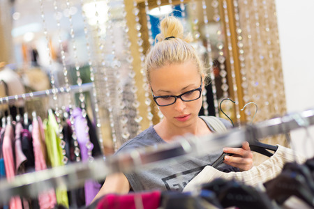 sales person: Woman shopping clothes. Shopper looking at clothing indoors in store. Beautiful blonde caucasian female model wearing black glases. Focus on model. Stock Photo