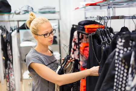 glases: Woman shopping clothes. Shopper looking at clothing indoors in store. Beautiful blonde caucasian female model wearing black glases. Focus on model. Stock Photo