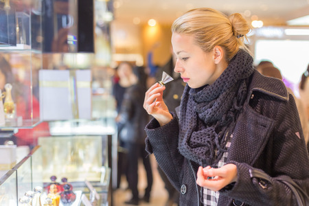 perfume woman: Beautiful blond lady testing and smelling perfume in a beauty store. Woman buying cosmetics in perfumery.