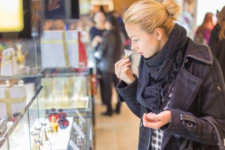 Prueba rubia hermosa dama y el perfume que huele en una tienda de belleza. Mujer compra de cosméticos en perfumería. Foto de archivo