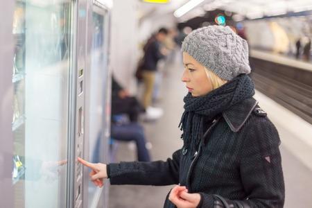 Terloops geklede vrouw draagt winterjas, kopen metro ticket bij de kaartautomaat. Stedelijk vervoer.