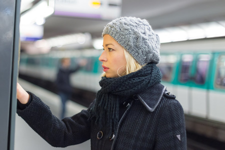 train ticket: Casually dressed woman wearing winter coat,buying metro ticket at the ticket vending machine. Urban transport.