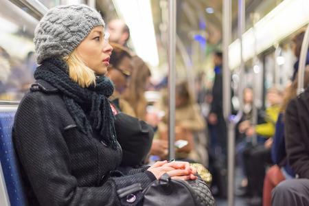 transport: Schöne blonde kaukasische Frau, trägt Wintermantel, Reisen mit der U-Bahn in der Hauptverkehrszeit. Öffentlicher Verkehr.