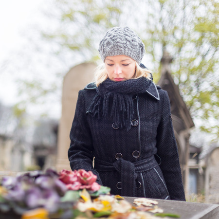 widow: Solitary woman mourning with her hand on gravestone, remembering dead relatives in on Pere Lachaise cemetery in Paris, France.