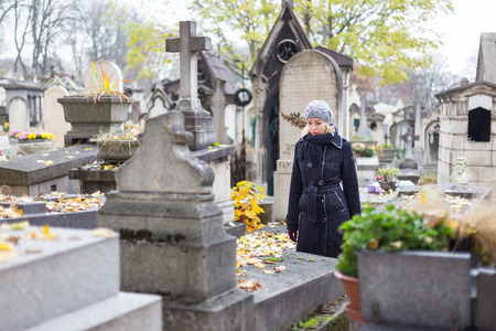 relatives: Solitary woman mourning by gravestone, remembering dead relatives in on Pere Lachaise cemetery in Paris, France.