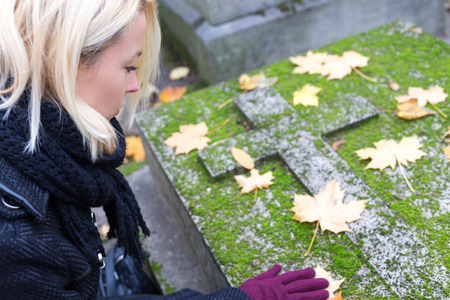 Solitary woman mourning with her hand on headstone, remembering dead relatives in on Pere Lachaise cemetery in Paris, France.