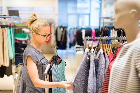 clothing shop: Woman shopping clothes. Shopper looking at clothing indoors in store. Beautiful blonde caucasian female model wearing black glases. Focus on model. Stock Photo