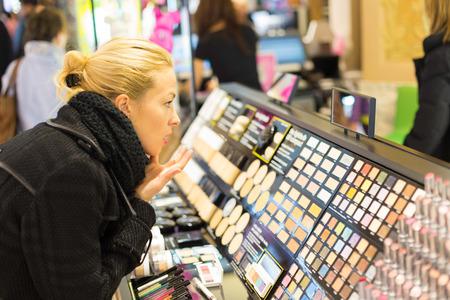 femme blonde: Belle tests de dame blonde et cosm�tiques d'achat dans un magasin de beaut�.