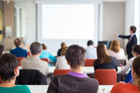 大学の講堂でプレゼンテーションを与えるスピーカー。参加者は講義を聴くと、ノートを作るします。白い画面でのブランドのためのスペースにコ 写真素材