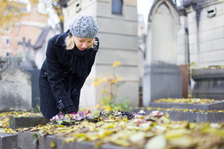 woman meditating: Mujer duelo solitario por l�pida, recordando familiares muertos en el cementerio de Pere Lachaise, en Par�s, Francia. Foto de archivo