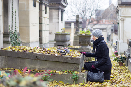 Solitary woman mourning with her hand on gravestone, remembering dead relatives in on Pere Lachaise cemetery in Paris, France.