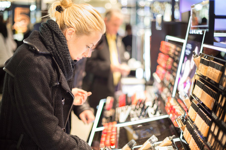 cosmetics products: Beautiful blond lady testing  and buying cosmetics in a beauty store.