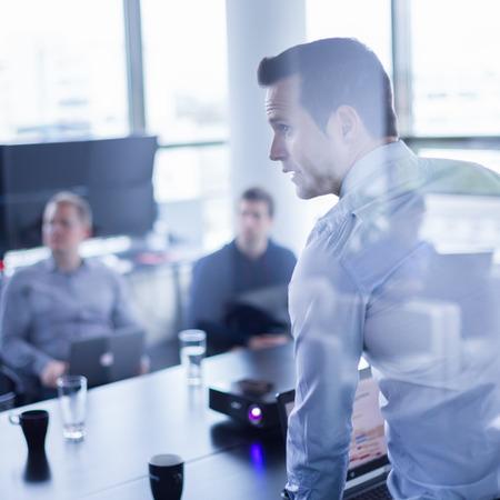 liderazgo empresarial: Hombre de negocios haciendo una presentación en la oficina. Ejecutivo de la empresa la entrega de una presentación a sus colegas durante la reunión o de la propia formación empresarial, explicando los planes de negocio a sus empleados.