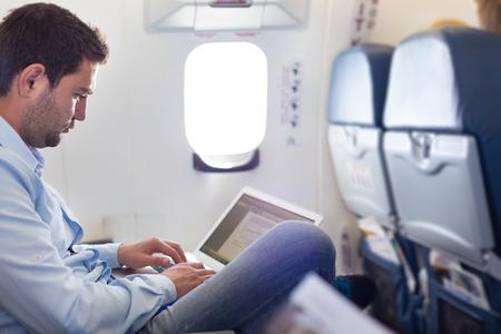 Lässig gekleidet mittleren Alter Mann arbeitet am Laptop in Flugzeugkabine während seiner Geschäftsreisen. Geringe Schärfentiefe Foto mit Fokus auf Geschäftsmann Auge.