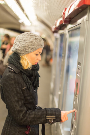 vending machine: Casually dressed woman wearing winter coat,buying metro ticket at the ticket vending machine. Urban transport.