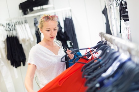 female clothing: Woman shopping clothes. Shopper looking at clothing indoors in store. Beautiful blonde caucasian female model wearing fashion sunglasses. Focus on model.
