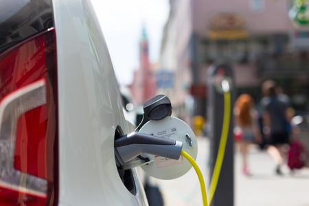 電気自動車を充電するための電源装置。 駅を充電する電気自動車。電気自動車充電中に差し込まれている電源のクローズ アップ。 写真素材